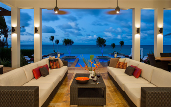 Two couches facing each other with a coffee table between them. The sea can be seen in the background