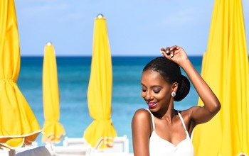 A black lady in a white sleeveless top is sitting with her left hand raised, smiling as she looks toward her left. In the background are yellow beach umbrellas and the ocean in the far background