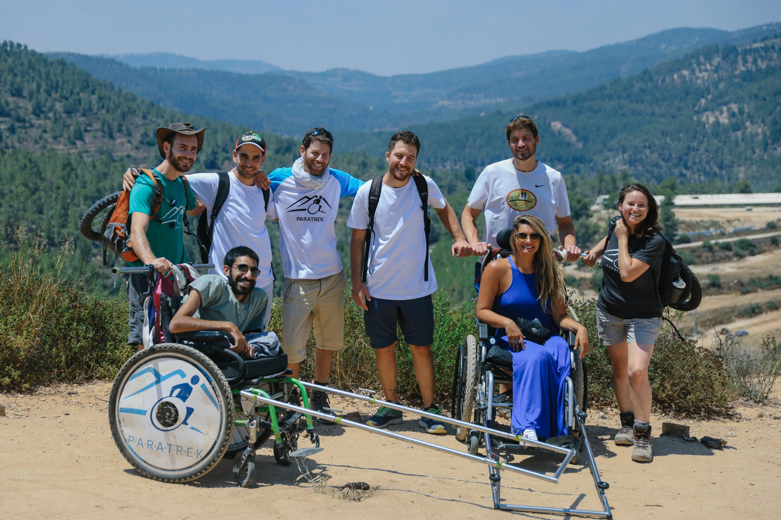 """<img src=""""Paratrek Group.jpg"""" alt=""""A smiling group of 6 people standing on a hill against a scenic mountain backdrop with 2 people sitting in Trekkers with smiles on their faces"""">"""