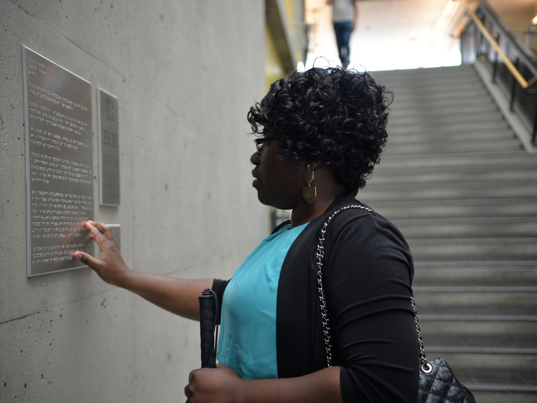 A visually impaired lady reading the braille on the wall