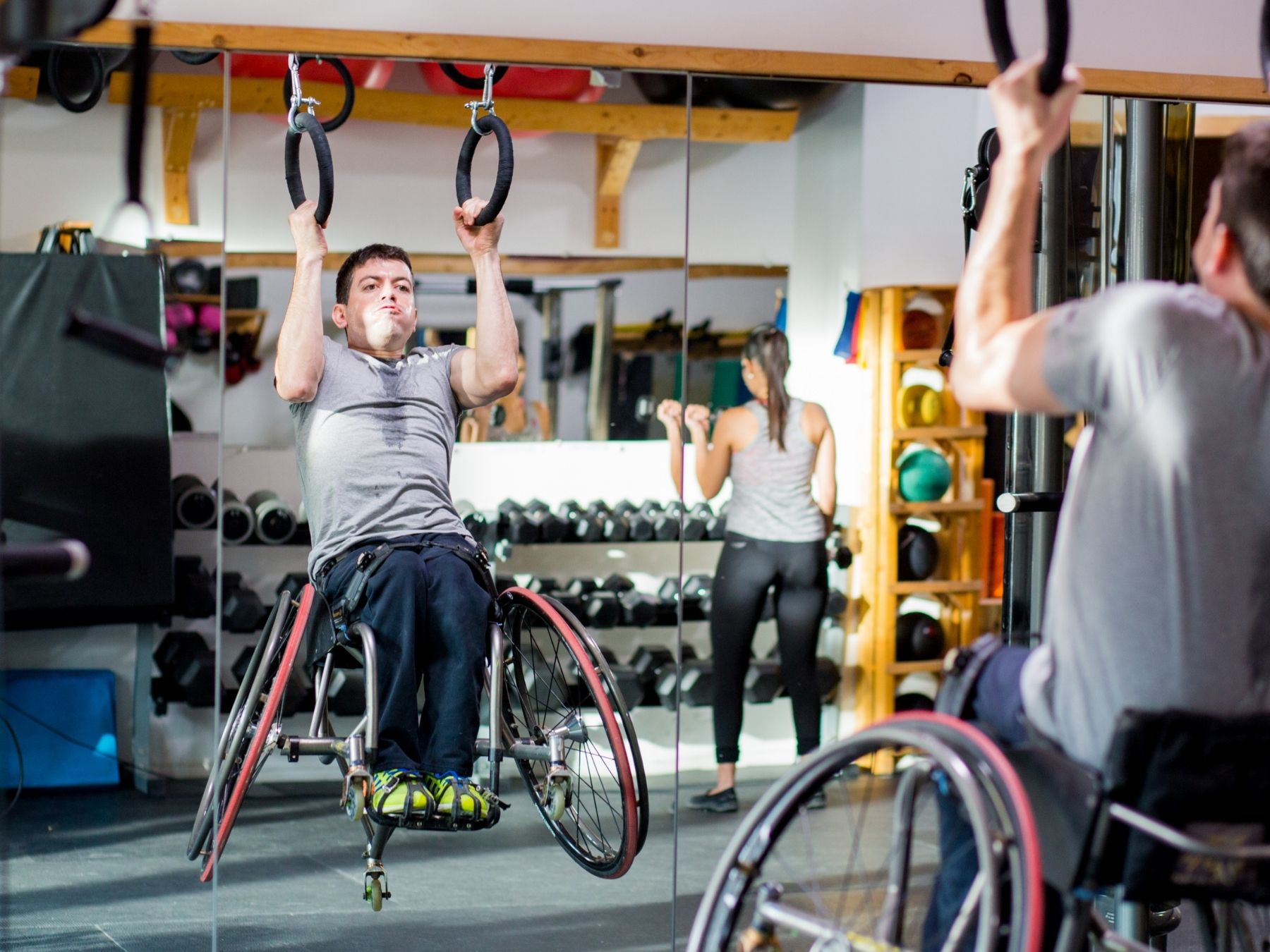 A man in a wheelchair, exercising at a gym