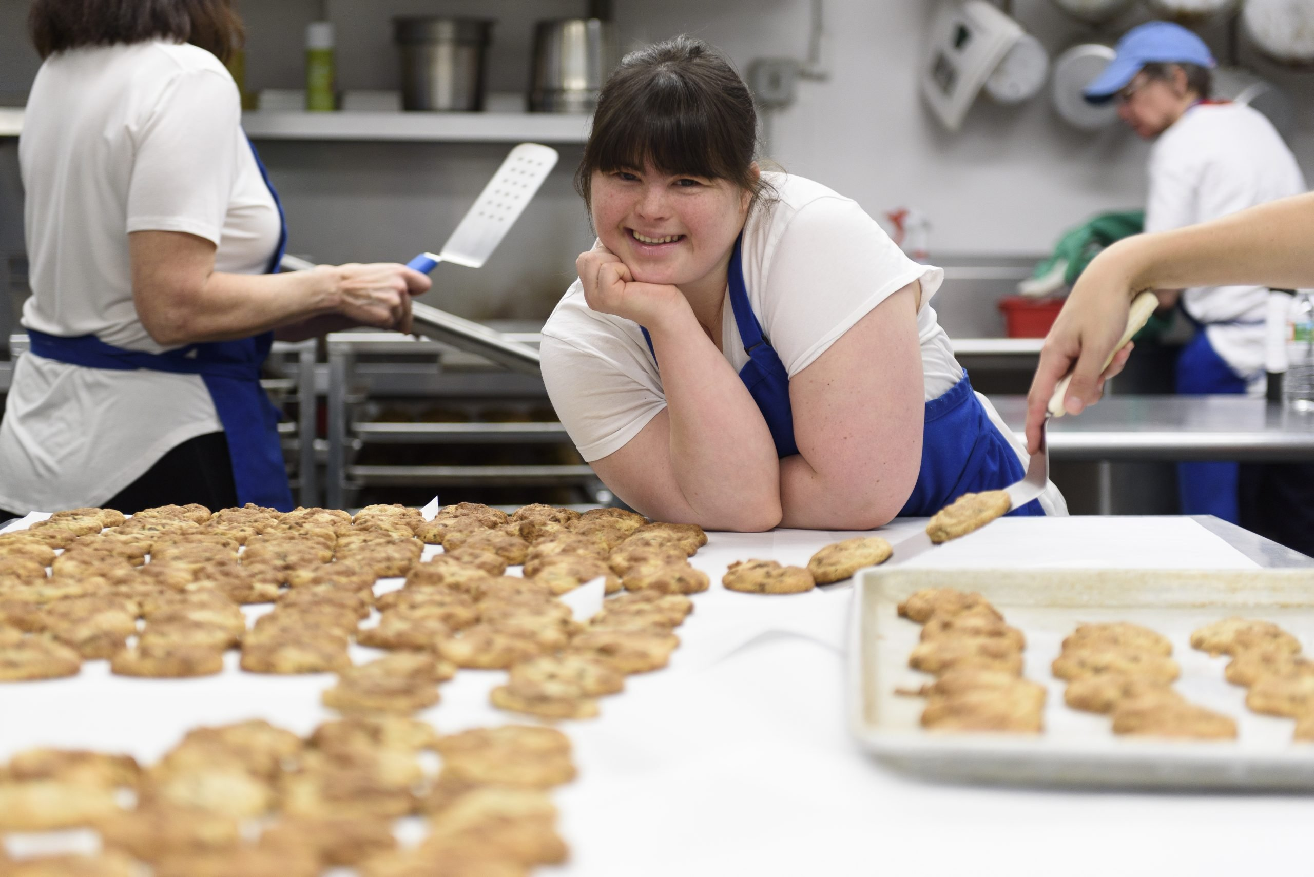 Collette Divitto at work. Workers are in the background and she is leaning on a table smiling, with cookies on the countertop in front of her