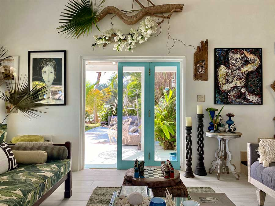 Charmaine's living room, adorned with driftwood and leafy fabric-covered couches