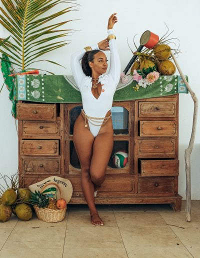 Woman in white swimsuit posing with coconuts